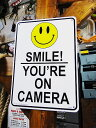 アメリカのプラスチックサインボード ヘビーオンスタイプ(アメリカの万引き監視中の看板/カメラがあるから笑顔で!) ■ 楽天1位 アメリカ雑貨 アメリカン雑貨 壁...
