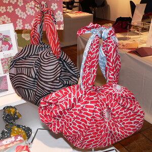 伊砂文様両面染め菊(アカ/セイジ)綿シャンタンふろしき(104cm)をバッグの形に結んだイメージ