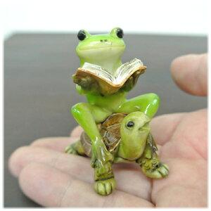 亀に乗りながら読書しているカエル